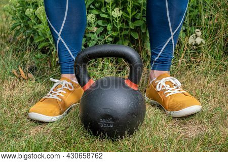 home fitness concept - weight training with a heavy iron competition kettlebell in a backyard
