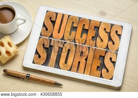 success stories concept - word abstract in vintage letterpress wood type on a digital tablet with a cup of coffee