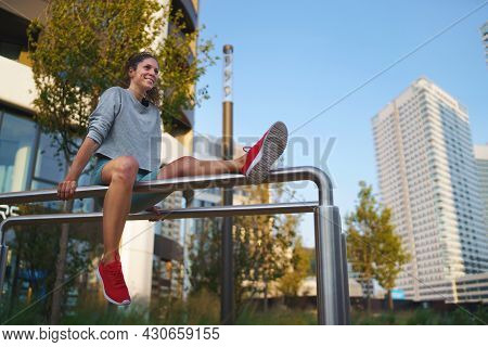 Mid Adult Woman Doing Exercise On Parallel Bars Outdoors In City, Healthy Lifestyle Concept.