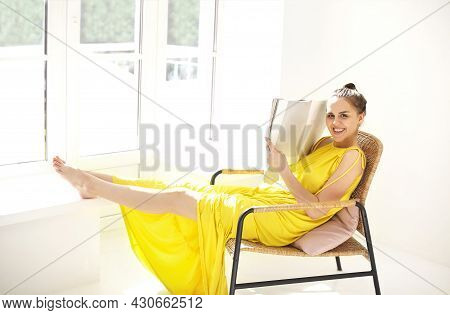 Cheerful Young Woman In A Yellow Dress Holding Book And Smiling At Camera While Sitting On Straw Cha