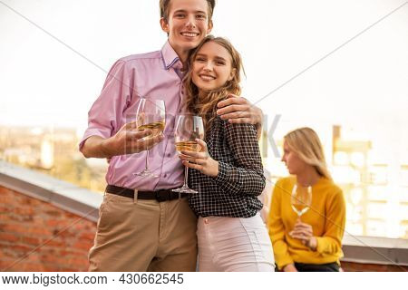 Happy Young Couple In Love Hugging Each Other On House Terrace, Holding Glasses Of White Wine, Smili