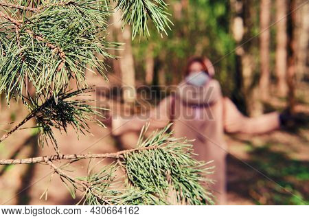 A Woman In A Medical Mask Walks Along A Path In The Spring, Selective Focus. The Concept Of The End