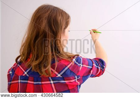 A Female Designer Draws A Line On A White Wall. Hand Draws The Future Arrangement Of The Room With A