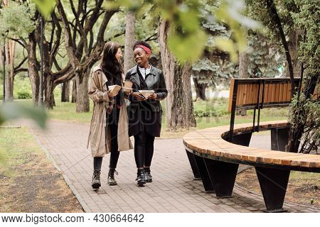 Two amorous intercultural girlfriends with snacks interacting while taking walk in park