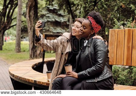Affectionate girlfriends making selfie while sitting on wooden bench in park