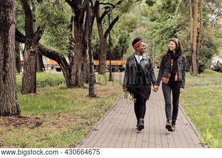 Affectionate lesbian couple in casualwear taking walk in public park at leisure
