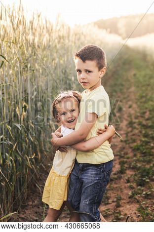 A Boy And Girl Brother And Sister Play In The Field In The Summer. Happy Summer Vacation. Boy And Gi