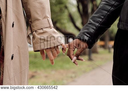Hands of amorous intercultural girlfriends taking walk in park at leisure