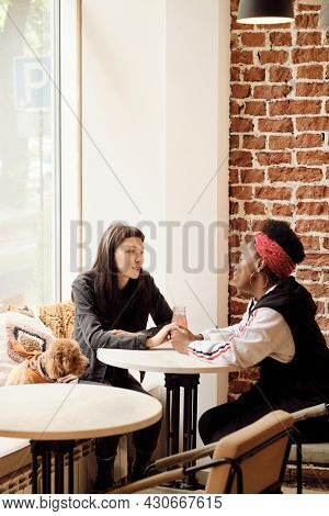 Amorous girlfriends in casualwear looking at each other while talking after lunch in cafe