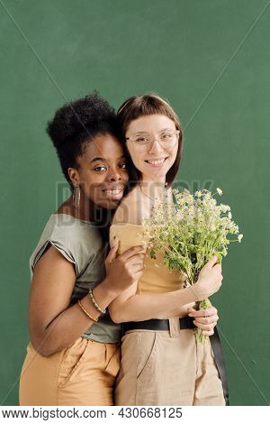 Two cute affectionate intercultural girlfriends in casualwear looking at camera