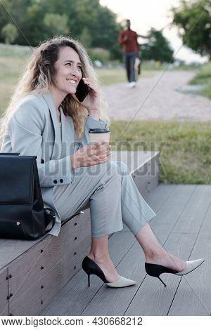 Young female white collar worker having drink and talking on smartphone while sitting on staircase