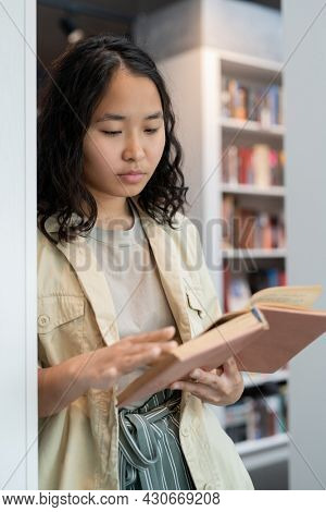 Clever student of college reading book while standing by bookshelf in library