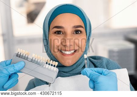 Dentist Doctor Choosing Right Emanel Color For Muslim Female Patient In Hijab