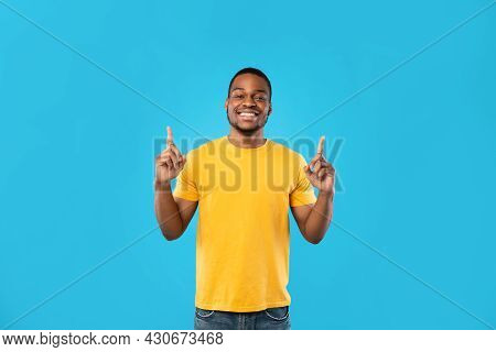 African American Male Pointing Fingers Upward Smiling Over Blue Background