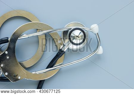 Medical Negligence Or Error Concept. Handcuffs And Stethoscope.