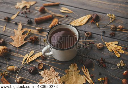 Warm Cup Of Tea On Background Of Autumn Leaves, Berries, Nuts, Anise, Acorns, Pine Cones On Rustic D