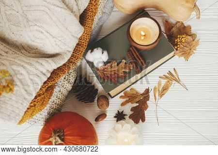 Autumn Flat Lay. Pumpkin, Cozy Sweaters, Autumn Leaves, Burning Candle And Vintage Book On White Woo
