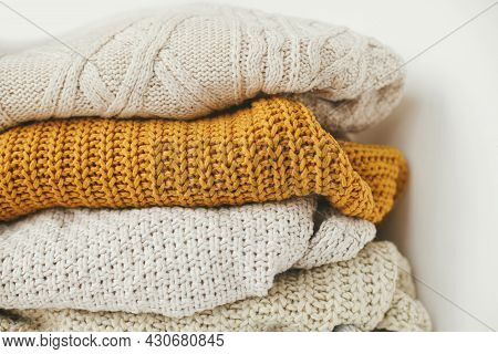 Cozy Knitted Sweater Background. Pile Of White, Yellow And Beige Knit Sweaters Close Up. Hello Autum