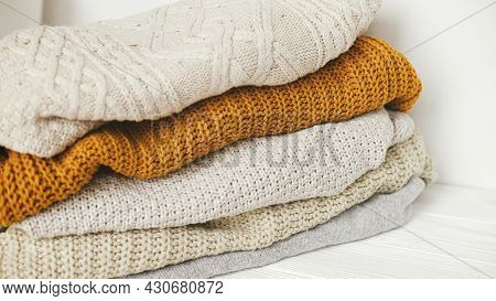 Pile Of White, Yellow And Beige Knit Sweaters Close Up In White Scandinavian Room. Cozy Knitted Swea