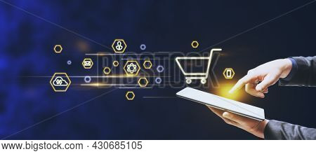 Businessman Hand Pointing At Tablet With Abstract Glowing Online Shopping Icons On Blurry Blue Backg
