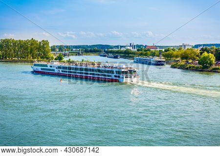 Speyer, Germany - August 21, 2021: Transport of goods on river Rhine, ferry and cruise vessel and boats