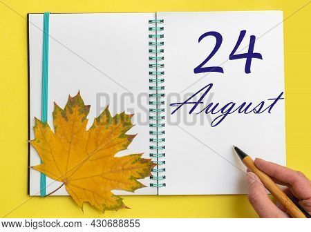 24th Day Of August. Hand Writing The Date 24 August In An Open Notebook With A Beautiful Natural Map
