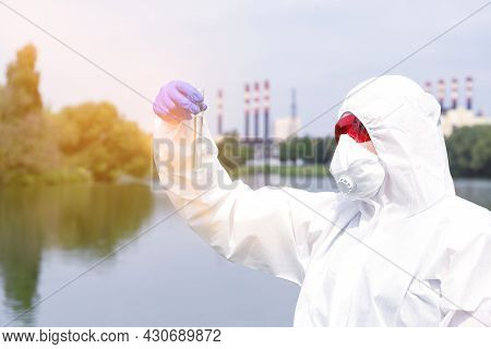 Sampling From Open Water. A Scientist Or Biologist Takes A Water Sample Near An Industrial Plant. Sa