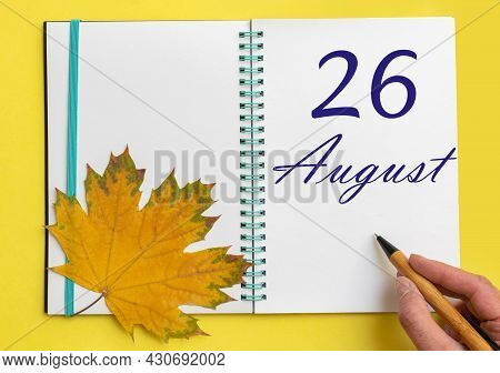 26th Day Of August. Hand Writing The Date 26 August In An Open Notebook With A Beautiful Natural Map