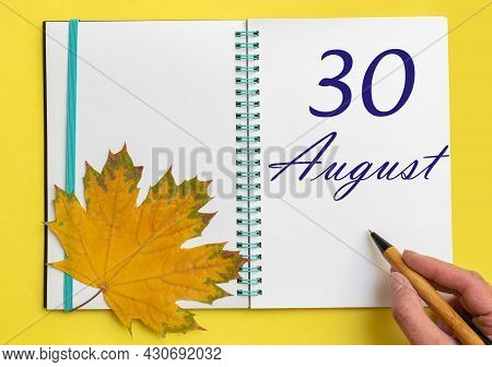 30th Day Of August. Hand Writing The Date 30 August In An Open Notebook With A Beautiful Natural Map