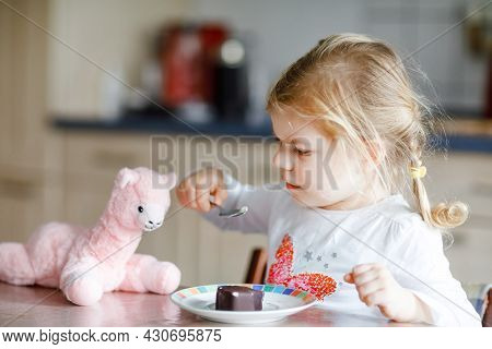 Cute Funny Toddler Girl Eating Chocolate Ice Cream At Home. Happy Healthy Baby Child Feeding Plush L