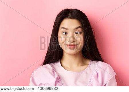 Close-up Portrait Of Funny Asian Woman Squinting Eyes And Making Silly Faces, Standing Against Pink