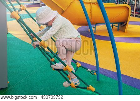 Girl Climbs The Rope Ladder On The Playground. I Love To Climbing. The Child On The Playground. Chil