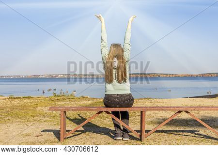 Hipster Young Woman Sitting On Bench By Lake Shore And Pulls Hands To Sun, Zen Like On Autumn Sunny