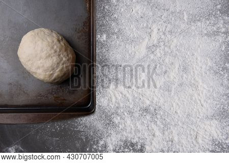 Baking Concept. A ball of bread dough ona baking sheet with rolling pin and counter top sprinkled with flour.