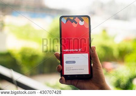 Woman Holding A Mobile Phone Against Urban Background With Vodafone Idea Vi Logo Indias Telecom Oper
