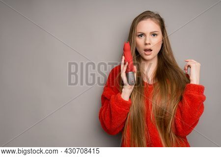 A White-skinned Girl With Long Hair In A Red Jacket Looks Surprised Holding A Vibrator Or A Dildo Fo