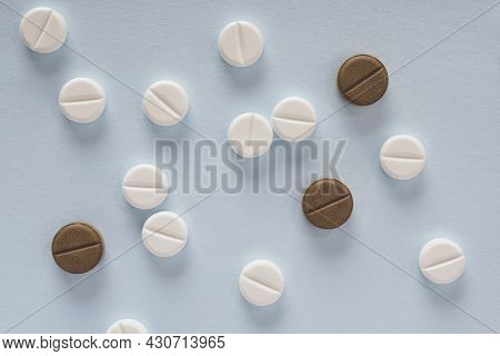 White And Brown Pills Lie On Light Blue Paper. Close Up. Flat Lay Background Or Backdrop About Medic