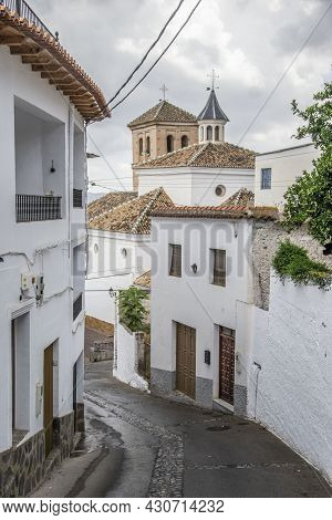 Sloping Street Of Válor Village In The Alpujarra With White Houses And The Mudejar Style Church