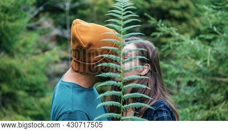 Couple Of Young People In Love Kissing Behind Fern Leaf In Forest. Unrecognizable Happy Man Hipster