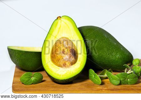 Halves Of Ripe Avocado And Micro Green On Wooden Board Served On Table, White Background, Healthy Oi
