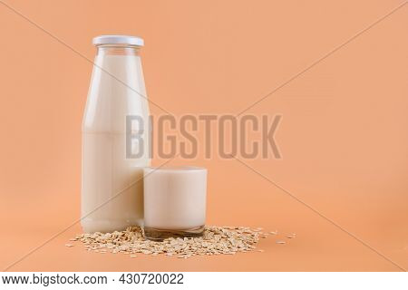 Trendy Vegan Non Dairy Alternative Milk. Oat Milk In Bottle And In A Glass On The Oat Flake On Paste