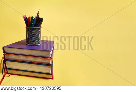 A Metal Pencil Holder With School Supplies On Stacks Of Multicolored Books. Teacher's Day Concept, L