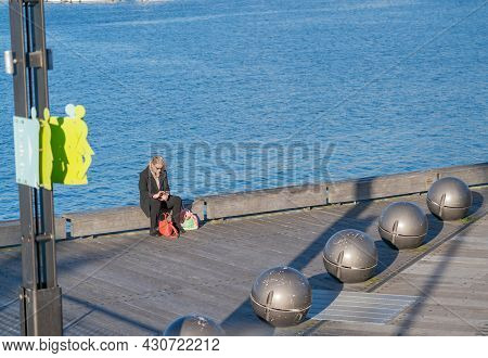 Wellington New Zealand - July 30 2021;woman Sits On Edge Of Great Harbour Way With Jupiter Sphere Bo