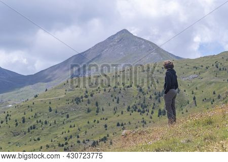 Young Woman In Mountain Clothes, Contemplating A Large Pyrenean Mountain In The Background, On A Sum
