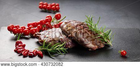 Two Fried Ribeye Beef Pieces On A Black Slate Board, Rare Degree Of Doneness. Appetizing Steak, Bann