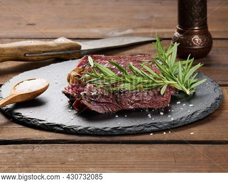 Fried Piece Of Beef Ribeye Cut Into Pieces On A Black Board, Rare Degree Of Doneness. Delicious Stea