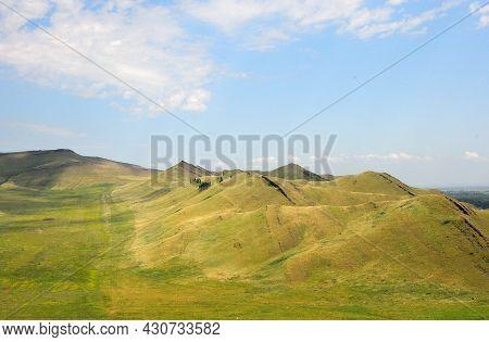 A Ribbed Mountain Ridge Runs Through The Steppe On A Summer Day.