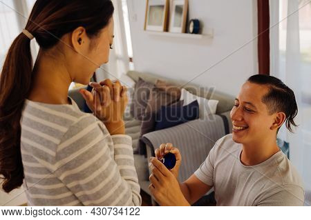 Young Man Proposing His Girlfriend With Engagement Ring At Home. Asian Woman Getting Surprised By He