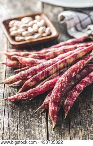 Cranberry beans. Borlotti beans. Beans pods on wooden table.