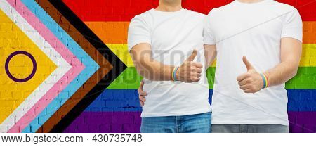 lgbtq, trans and intersex rights concept - close up of male gay couple hugging and showing thumbs up over rainbow progress pride flag on background